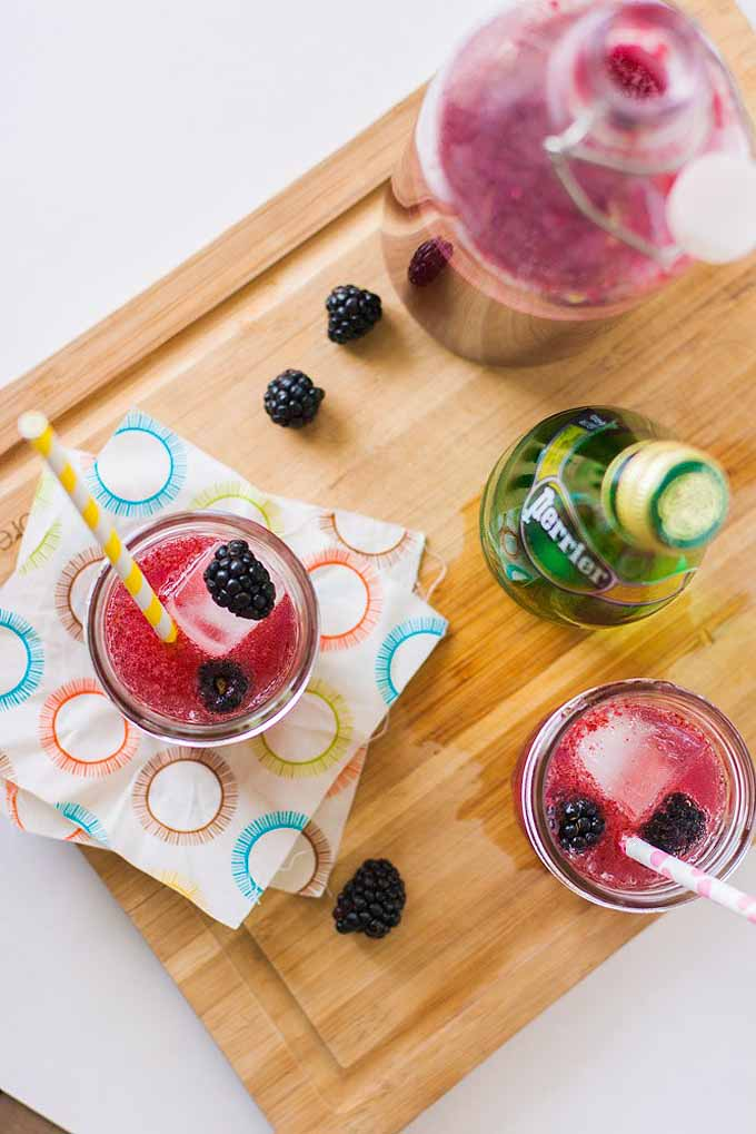 Top-down view of two blackberry and lemon cocktails, plus loose berries and a bottle of Perrier, sitting on patterned cocktail napkins on a bamboo cutting board.