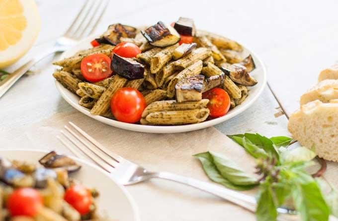 Oblique view of a Caramelized Eggplant Pesto Pasta dish on a white ceramic plate.