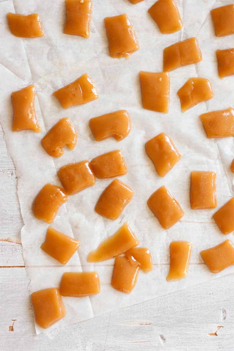 Square portions of brownish orange homemade caramel, on waxed paper.