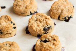 Six blueberry scones, on white parchment paper.