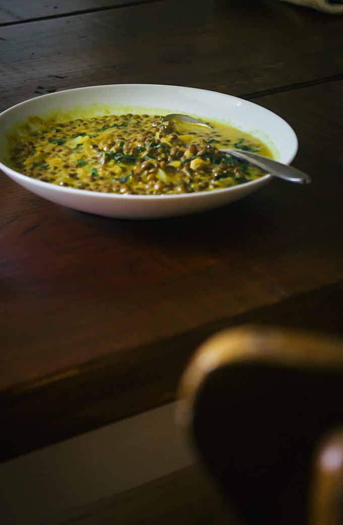 A bowl of french lentil soup set on dark wooden table.