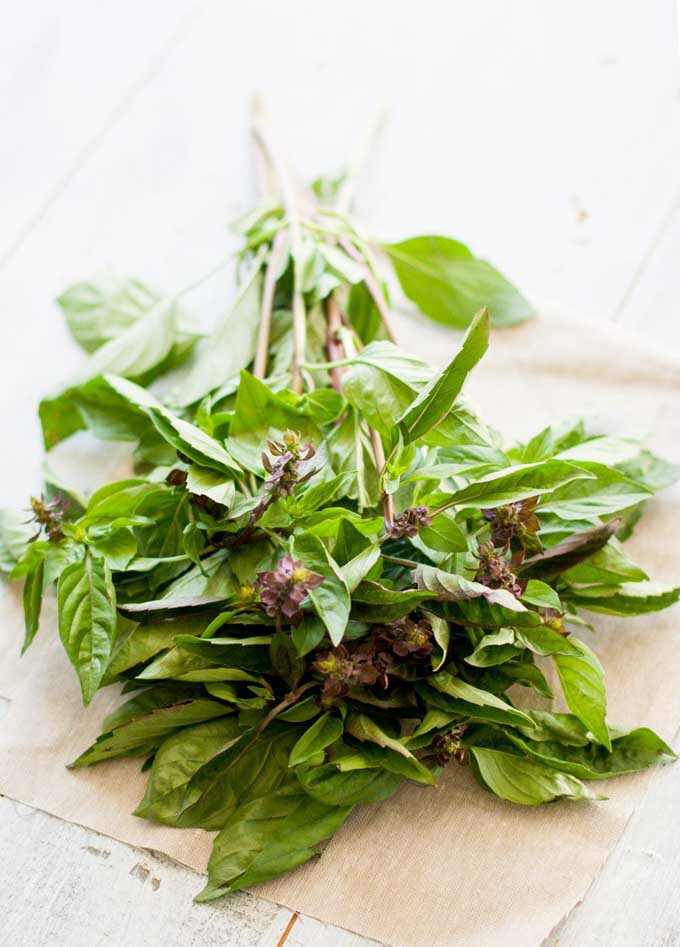 Green fresh basil leaves on a white linen napkin.