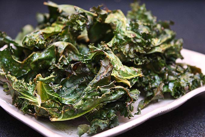Horizontal image of a white platter with a mound of kale chips.
