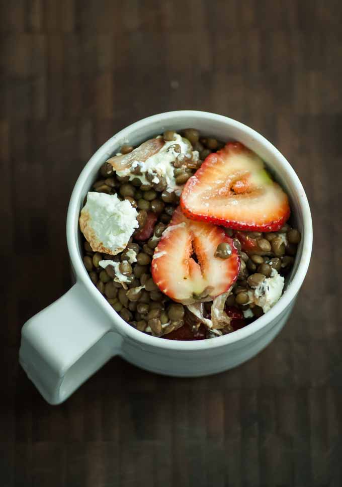 Top down view of a white mug with a recipe containing Lentils with Shallots, Strawberries, and Goat Cheese and flavored with balsamic vinegar.