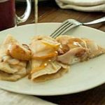 Light and Buttery Nut Flour Crepes with Roasted Fruit on a white porcelain plate.