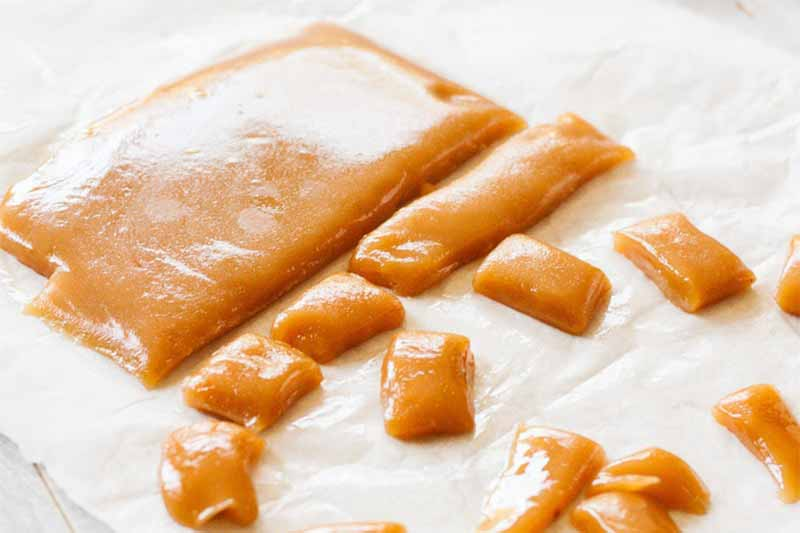 Homemade caramel being cut into bite-sized chunks, on a crumpled piece of waxed paper.