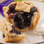 A close up of a broken open mini blueberry pie showing the gooey insides.
