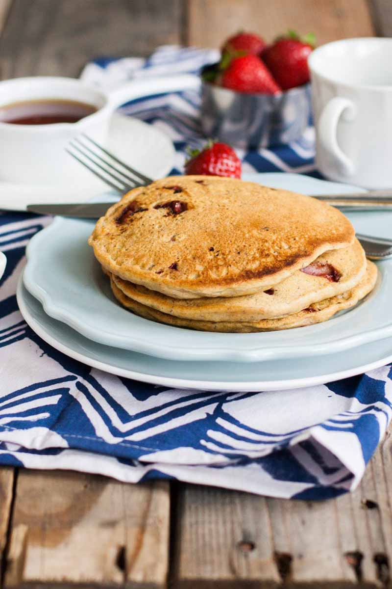 A stack of light and fluffy vegan pancakes on a ceramic plates sitting on a blue and white folded tablecloth.