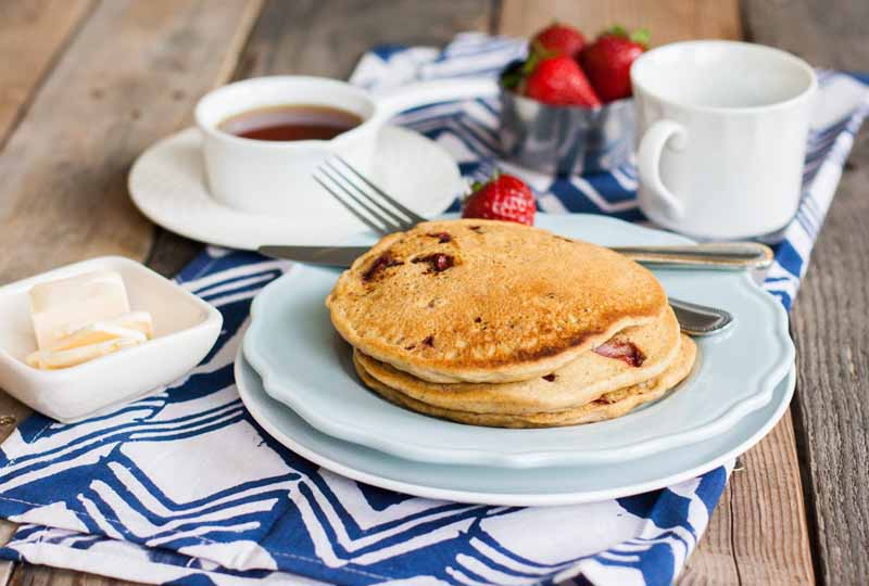 Oblique view of a stack of pancakes on a ceramic plate sitting on a folded blue and white tablecloth on a rustic wooden table