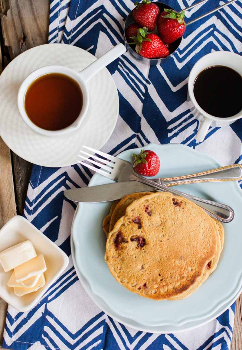 Top down view of a stack of whole grain vegan pancakes with vegan butter, maple syrup, and cup of coffee on a white and blue tablecloth.