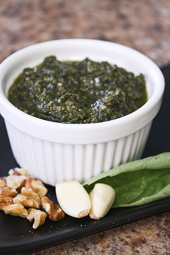Vertical image of a white ramekin with a dark pesto on a black board next to walnuts, garlic cloves, and basil on a granite surface.