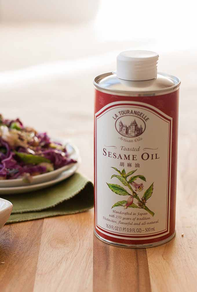 A large bottle of sesame seed oil sitting on a wooden butcher block. A plate of purple cabbage slaw is in the background.