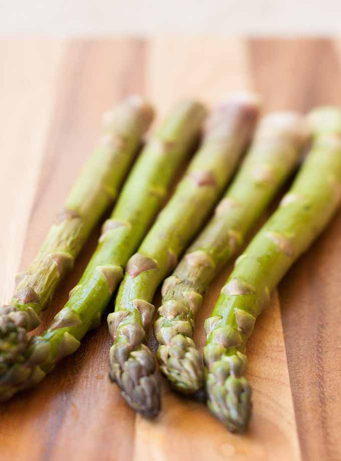 5 spears of asparagus laying on an acacia wood cutting board.