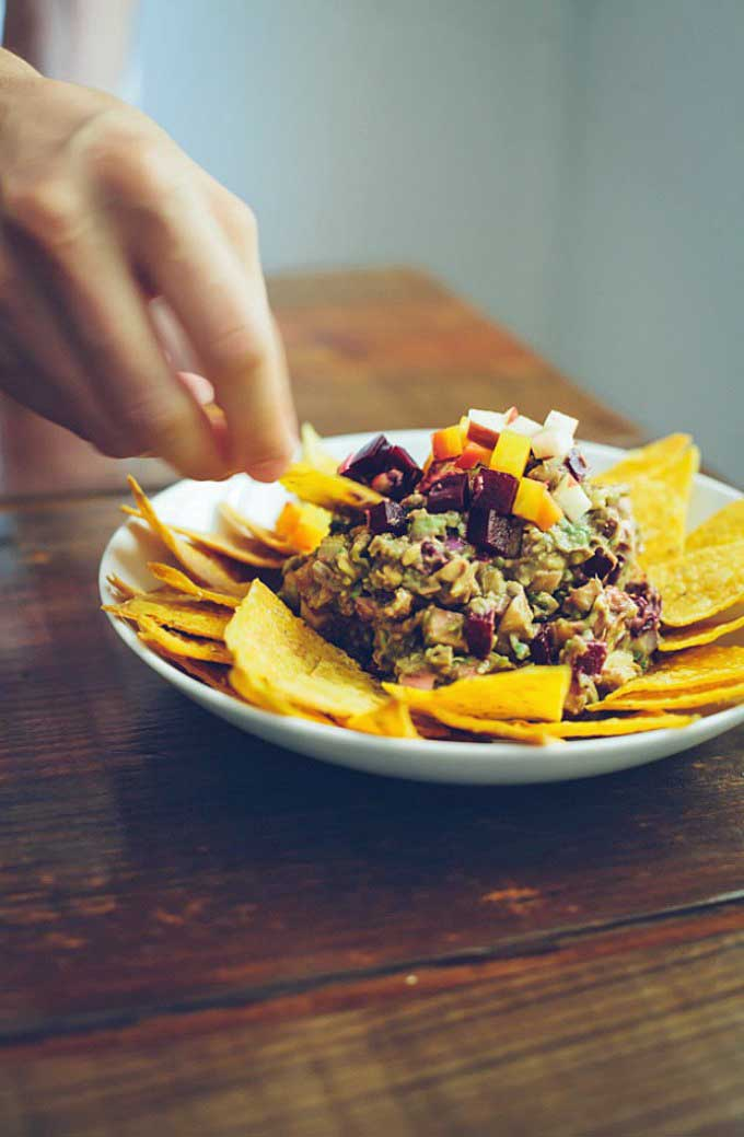 A human hand uses a homemade tortilla chip to scoop up some rainbow guacamole from a white serving dish.