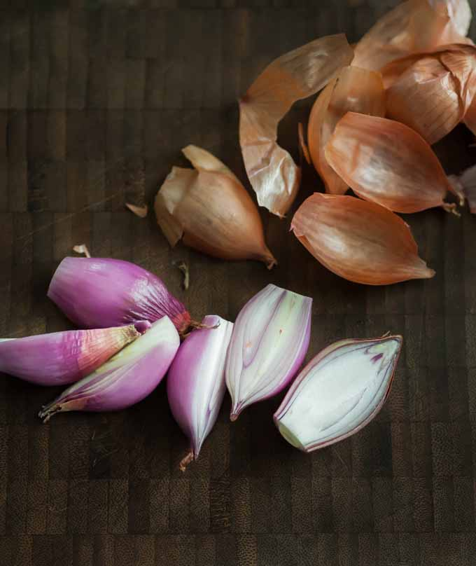 Fresh and raw peeled purple shallots on a dark wooden background.