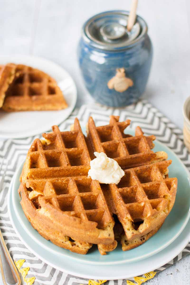 Golden brown homemade waffles on a light blue plate, topped with a dollop of honey butter, with another cut in half and stacked on a white plate in shallow focus in the background, beside a blue honey pot with a wooden dipper and a decorative bee on the front, on a white and gray chevron patterned cloth with yellow embroidery around the border.