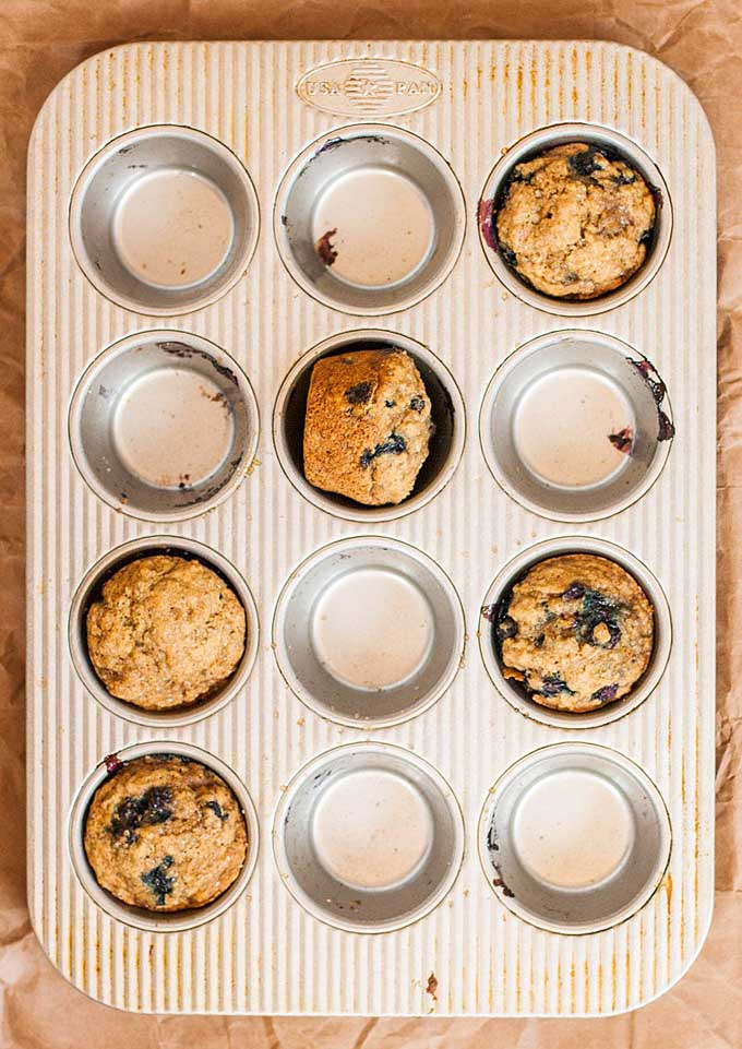 Top-down view of 5 vegan blueberry banana muffins sitting in a baking pan.