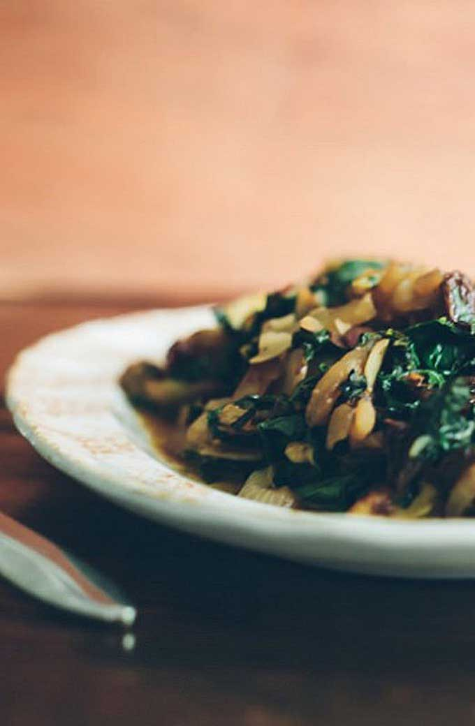 Close up of Sautéed Swiss Chard with Caramelized Onions, Almonds and Raisins on a white ceramic plate.