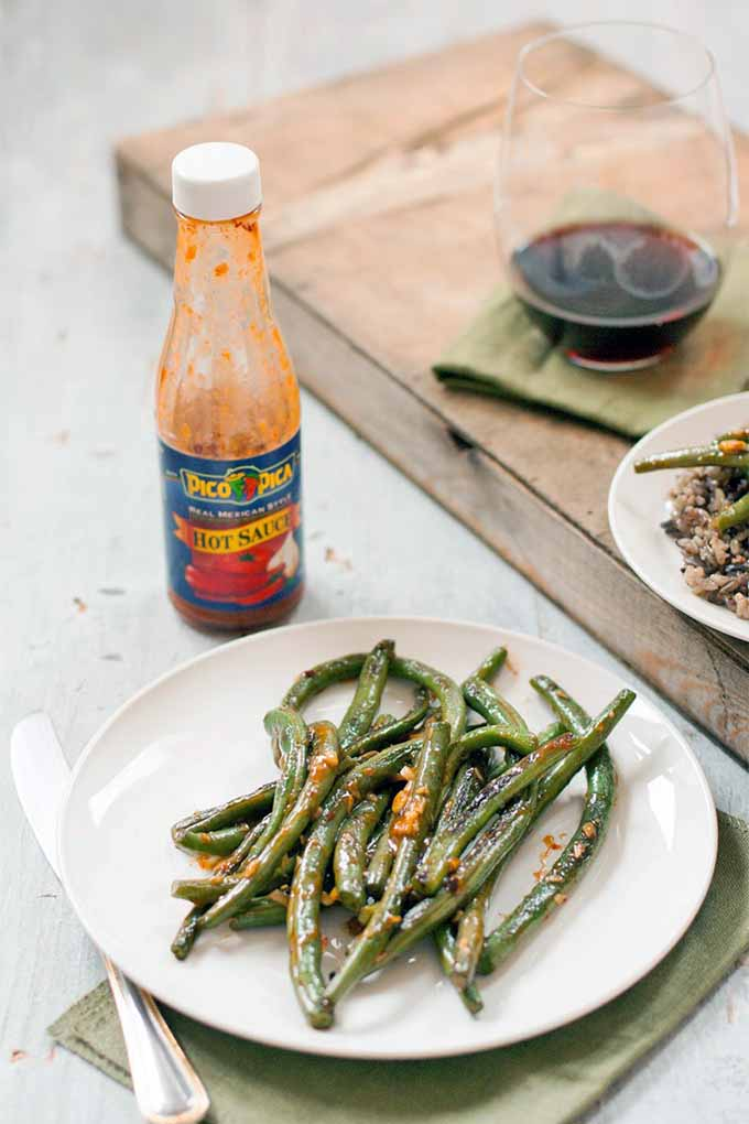A white plate of green beans with hot sauce and minced garlic on a folded napkin with a knife, on a gray wooden surface with flaking paint, next to a bottle of hot sauce and a board topped with another napkin, a stemless glass of red wine, and another plate of beans.