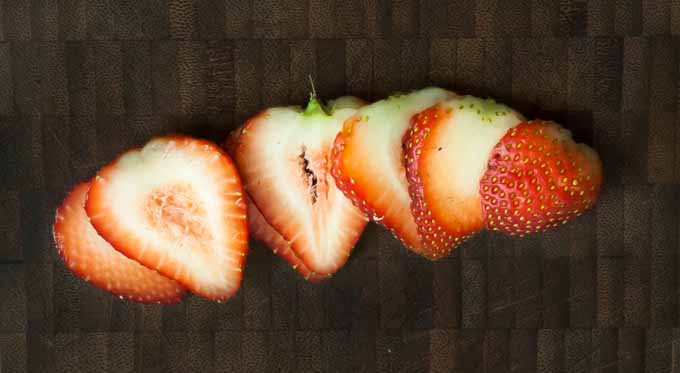 A thinly sliced strawberry on a dark wooden background.