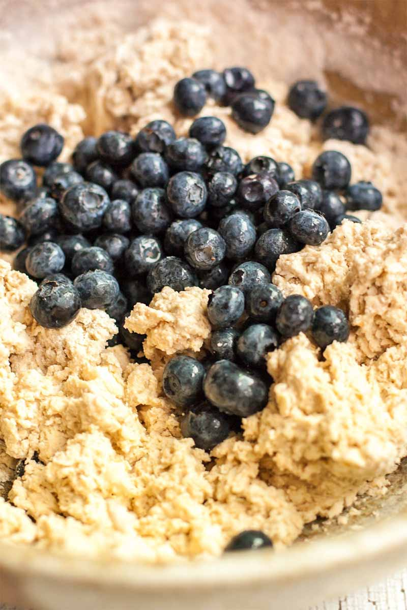 Closeup of a tan dough mixture with fresh blueberries on top.