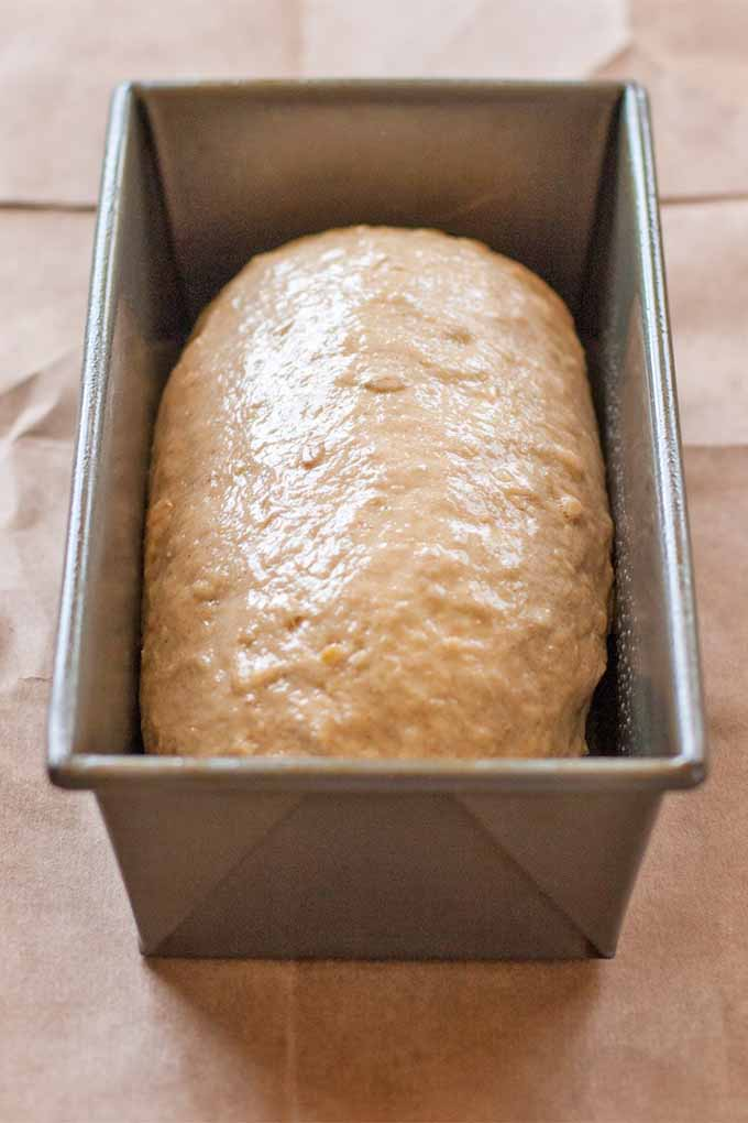 A loaf pan filled with proofed dough on a large piece of brown paper.