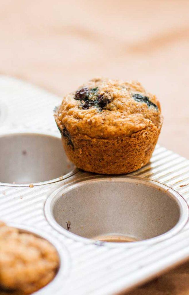 Closeup of a single whole wheat blueberry banana muffin.