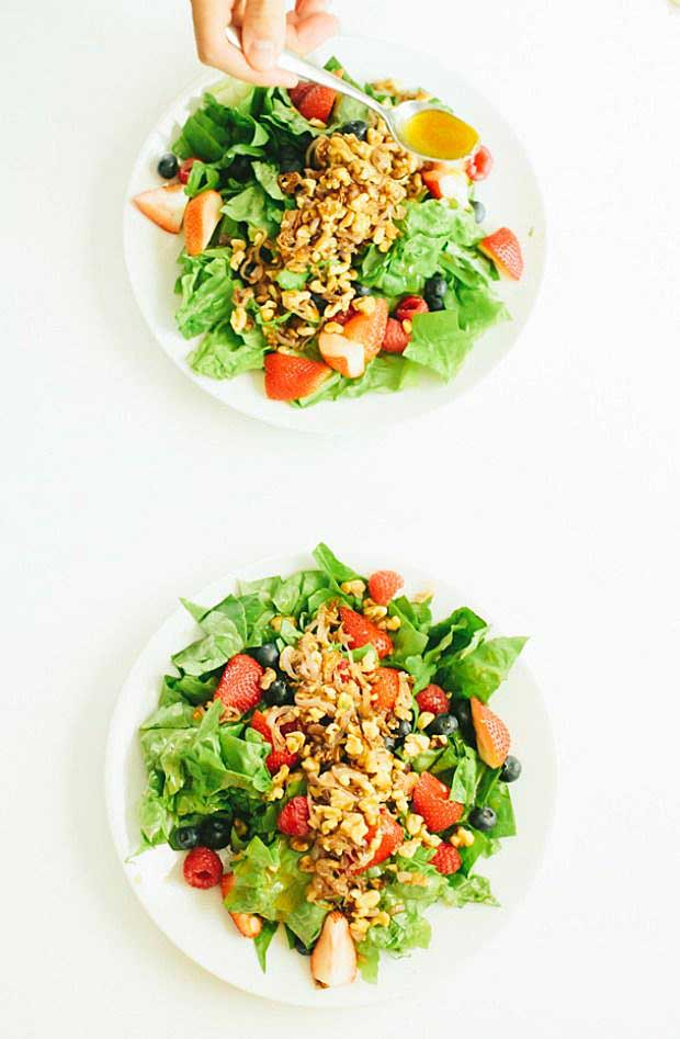 Top-down view of two leaf lettuce salads made with strawberries, raspberries, blueberries, shallots, and walnuts.