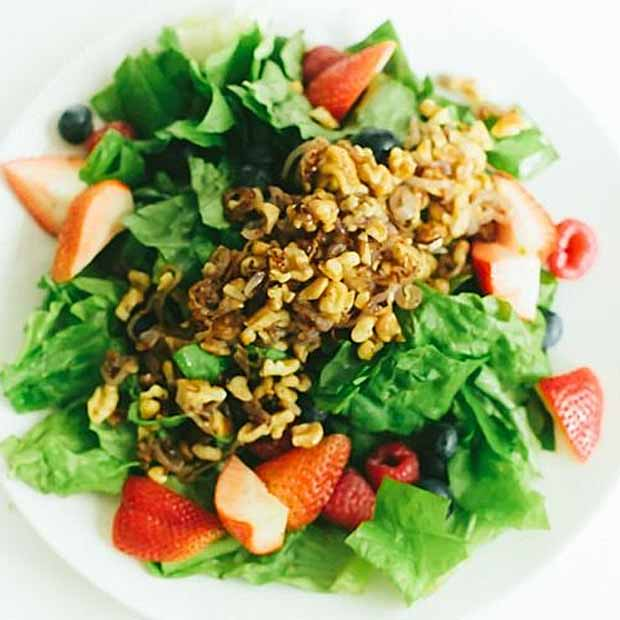 Overhead view of a Triple Berry Salad with Sauteed Shallots and Walnuts and Cayenne-Honey Vinaigrette on a white, porcelain plate.