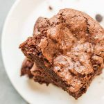 Top-down stack of three brownies on a white plate, with a few scattered chocolate chips, on a gray background.