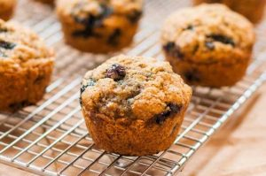 Close up of a batch of whole wheat blueberry banana muffins on a cooling rack.