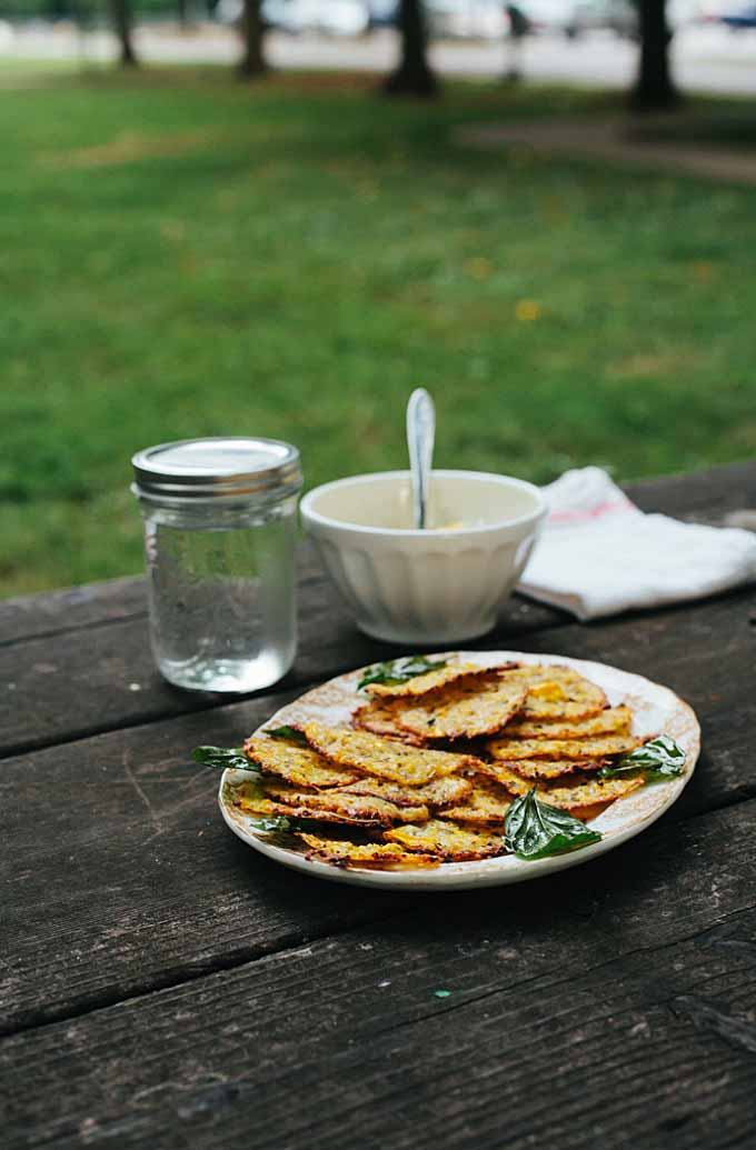 A white, platter full of cheesy zucchini crispies on an outside wooden picnic table.