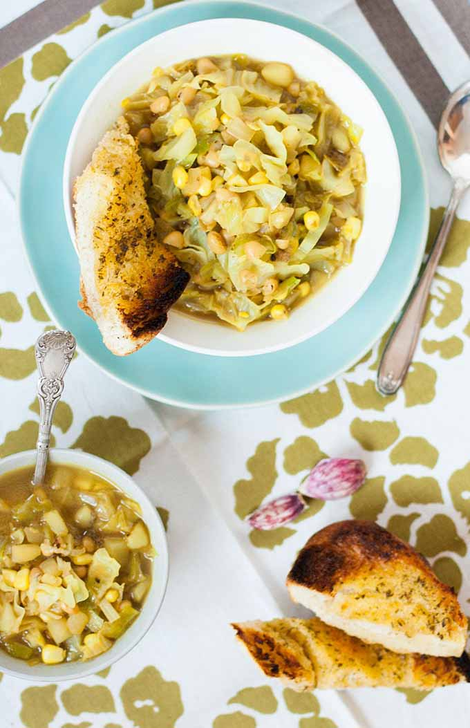 Top-down view of two bowls of curried cabbage and corn soup, with white beans and yellow onion, sitting on a patterned tablecloth.