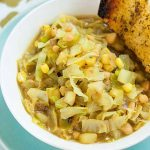A white ceramic bowl full of curried cabbage and corn soup sitting on a patterned table cloth with a chunk of crusty garlic bread.