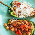 Two halved green poblano peppers filled with a vegetarian quinoa mixture with cheese sprinkled on the one towards the top of the frame, on a shiny aqua-colored ceramic plate.