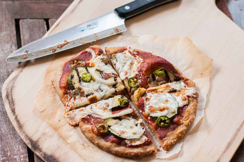 A grilled zucchini pizza on a wooden pizza peel with a Mac chef's knife above it.