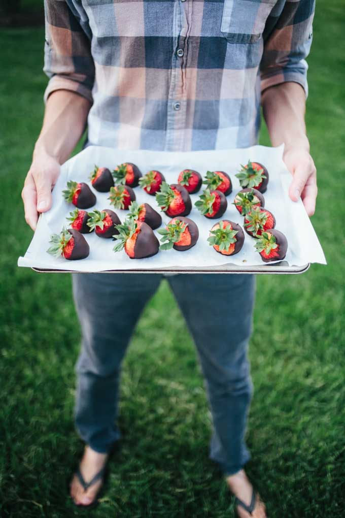 A man stands with a rimmed baking tray of homemade chocolate covered strawberries.
