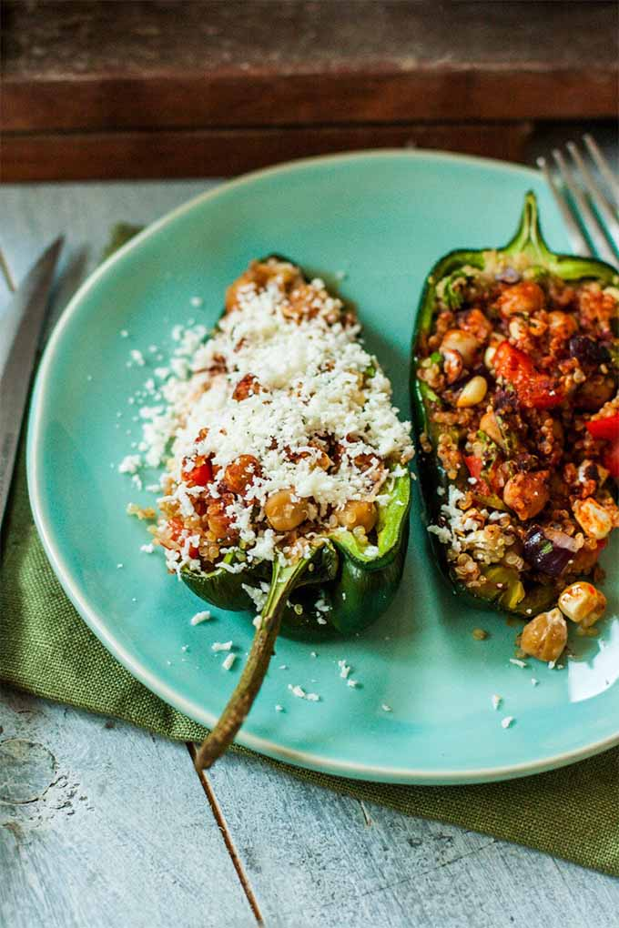 Vertical image of two halves of a green poblano filled with a mixture of quinoa, garbanzo beans, and vegetables, with the one on the left topped with crumbled cotija cheese, on a light aqua colored plate, on top of a green folded napkin on a white stained wood surface.