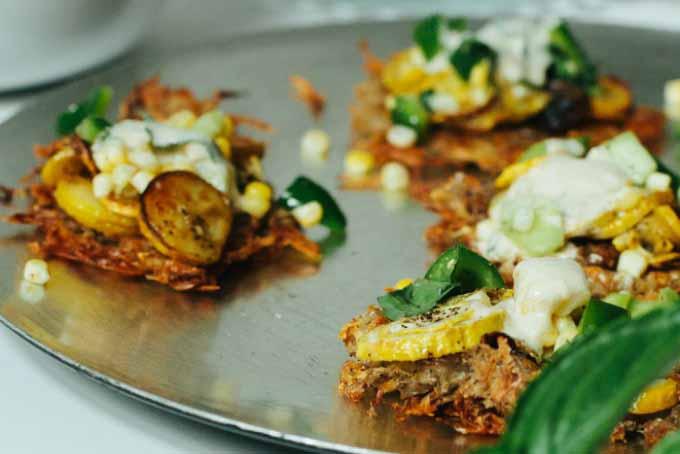 Close up of Potato Fritters with Roasted Zucchini, Cucumber Corn Salad & Cumin Dill Yogurt Sauce on a metal baking pan.