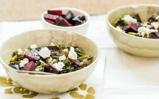Three white ceramic bowls, two large and one small. The former are filled with kale, farro, beets, and goat cheese. The latter contains roasted beets. on a white tile surface with a green and white napkin with a floral pattern.