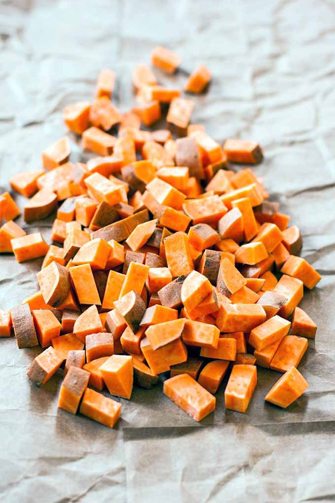 A pile of diced, raw orange sweet potato with brown skin, on a wrinkled piece of brown butcher craft paper.