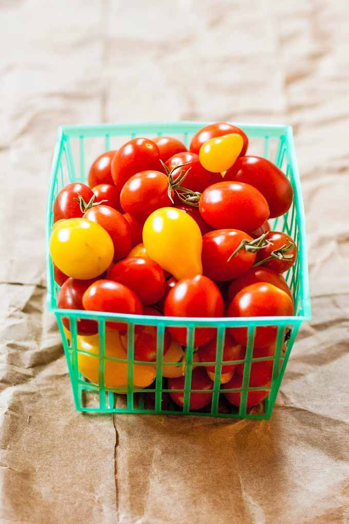 Vertical image of a square plastic basket of red grape tomatoes and yellow pear-shaped tomatoes, on a crumpled piece of brown butcher paper.