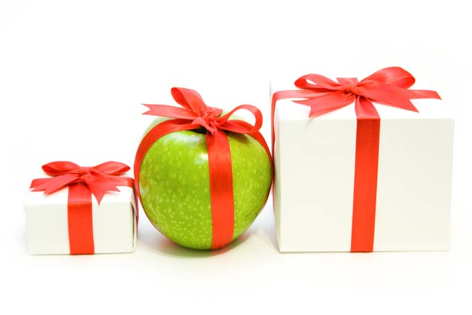 Green apple wrapped in red lace ribbon with small white gift box on left and larger gift box on right both wrapped in red ribbon. Isolated background.