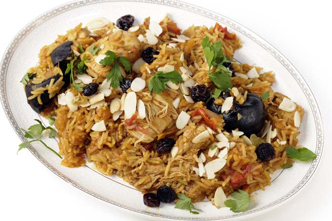 Kabsa rice and chicken on a white plate; isolated background