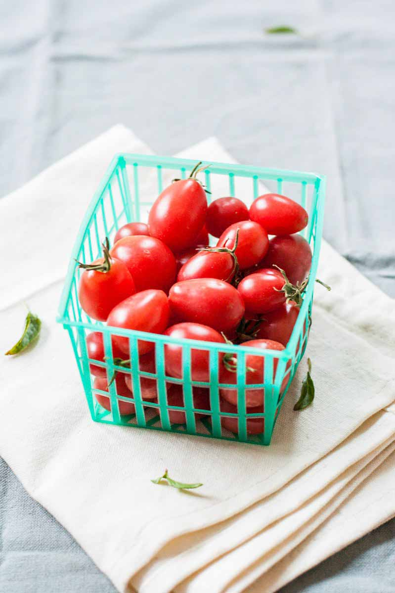 A small plastic mesh pint basket full of fresh cherry tomatoes on a white linen table cloth.