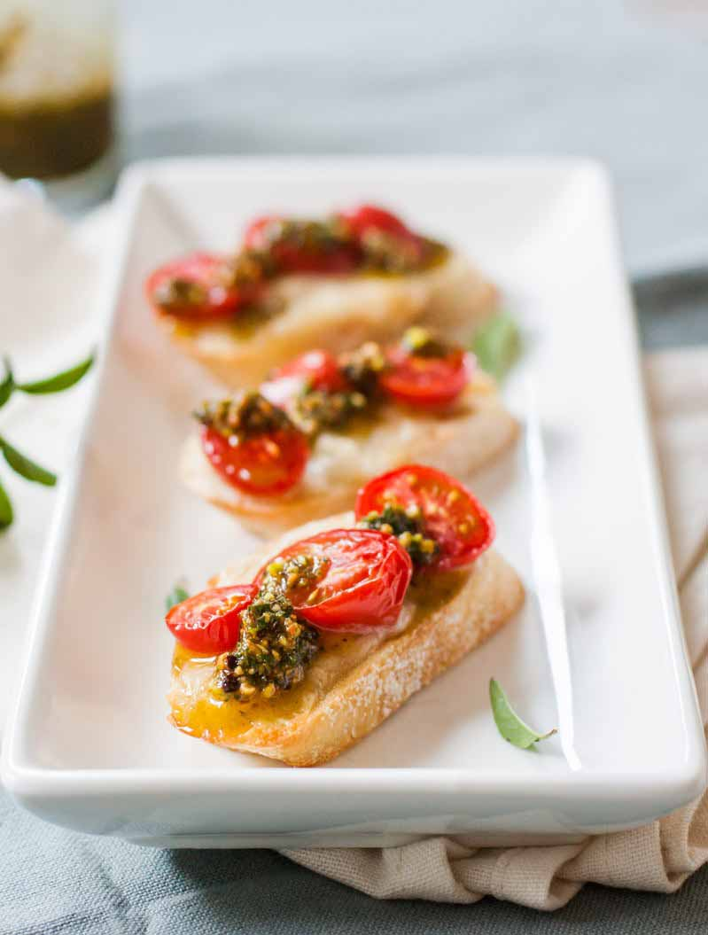 Oblique view of crusty baguette slices with melted soft cheese, roasted cherry tomatoes, and a pistachio pesto sauce. Selective focus with a diffused background.