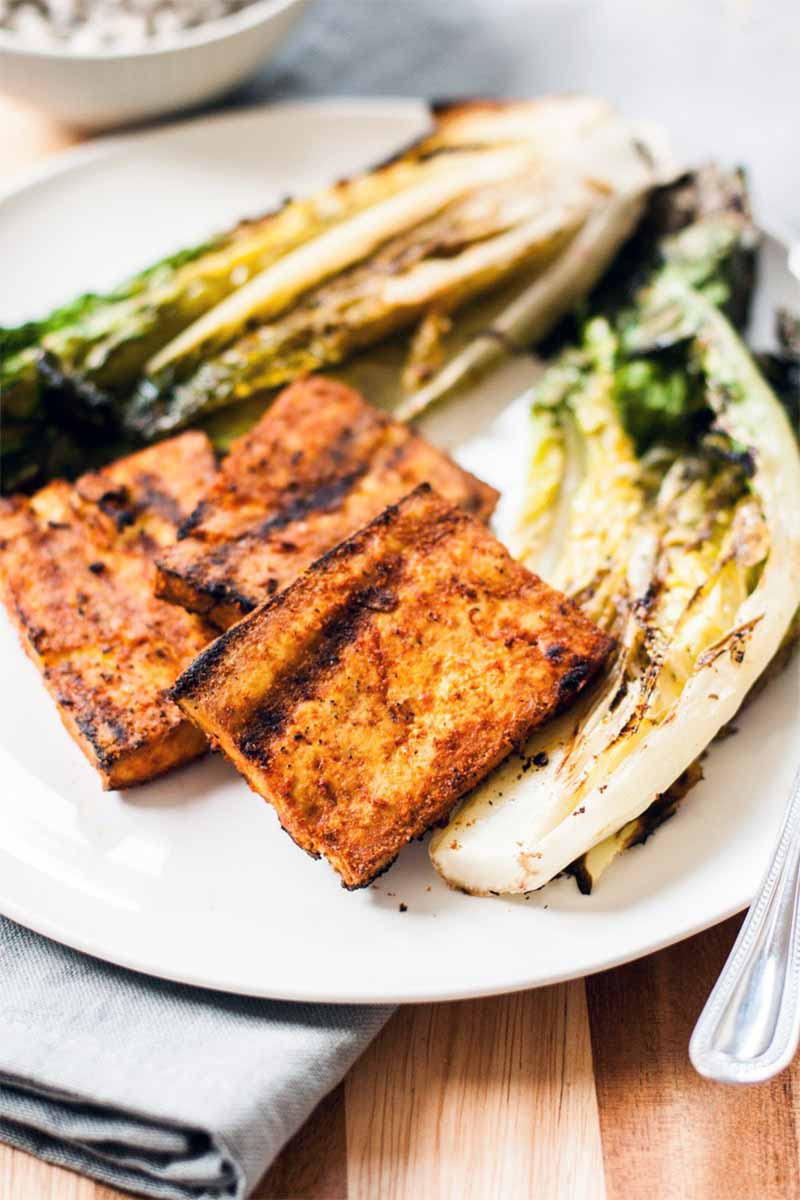 Three pieces of grilled tofu coated with orange spices, on a white plate with two pieces of grilled romaine lettuce, on a folded gray cloth napkin with a fork, with a small bowl of cooked grains in the background, on a wood surface.
