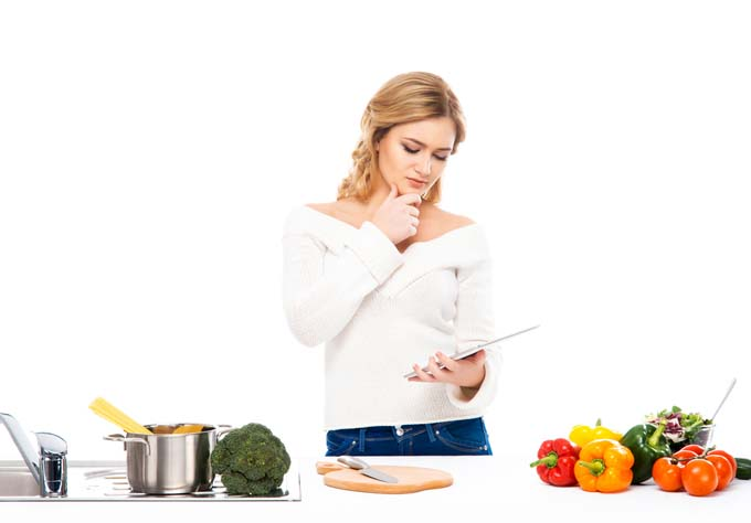 novice blonde female cook studies ipad to figure out how to cook here meal. White table with stainless stock pot, yellow and red bell peppers, brocoli, cutting board, and knife. isolated background.