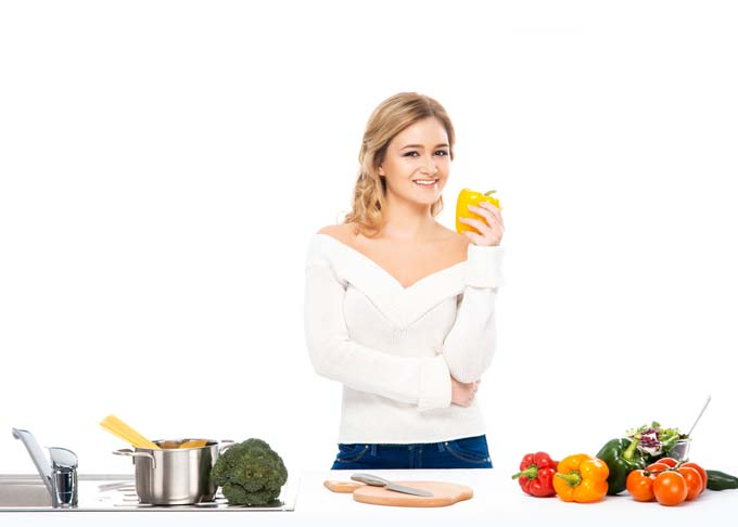 Young house wife had figured out how to cook her meal; ingrediants and cookware laid on on white table. She is holding yellow bell pepper in her hand with a smile on her face.