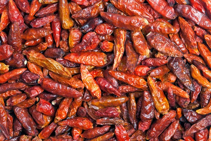 Dried Cayenne pepper texture background. Also called Guinea spice cow-horn pepper aleva bird pepper red pepper hot chili pepper. Used to flavor dishes and for medicinal purposes.